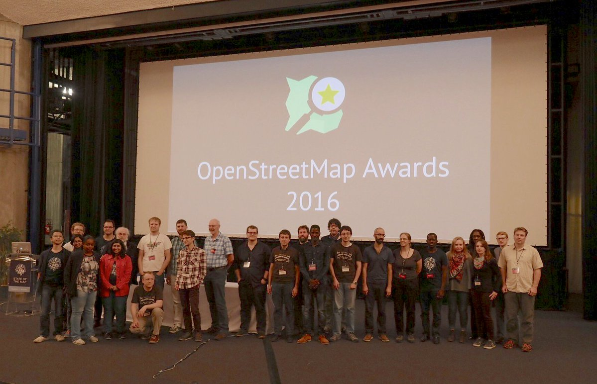 A group photo of all the nominees on the stage of the State of the Map conference