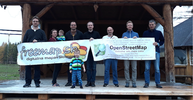 """Outdoor photograph of Freemap SK members, holding large """"Freemap.sk"""" and """"OpenStreetMap"""" banners."""